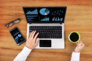 Analyzing business chart on laptop