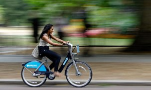 A woman rides a Barclays cycle hire bike in London.